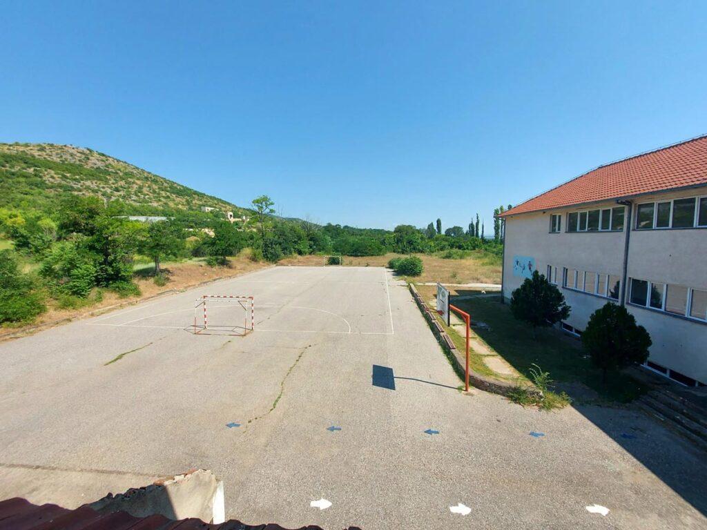 Двор на училиште со асфалтирано фудбалско игралиште.