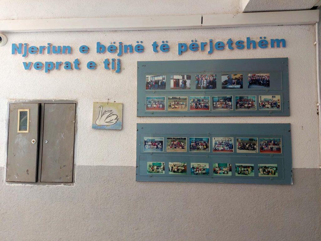 Слика од внатрешноста на училиштето, во која има табла со ученички слики.
